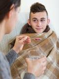 Madre que trata al adolescente con el jarabe en casa Fotografía de archivo