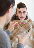 Madre que trata al adolescente con el jarabe en casa Imagen de archivo libre de regalías
