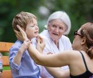 Madre que trata el rascado en la barbilla del ` s del hijo foto de archivo