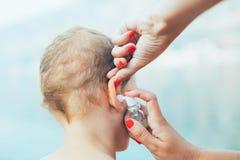 Madre que trata la infección del oído del niño pequeño Fotografía de archivo libre de regalías
