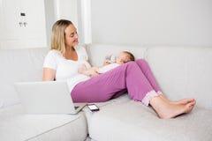 Madre que usa el ordenador portátil mientras que alimenta a su bebé con la botella de leche Imagen de archivo libre de regalías