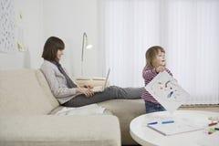 Madre que usa el ordenador portátil y a la hija que dibujan en casa Foto de archivo libre de regalías
