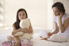 Madre que usa el teléfono móvil con la hija que detiene a Teddy Sitting On Bed Imagen de archivo libre de regalías