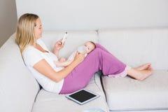 Madre que usa el teléfono móvil mientras que alimenta a su bebé con la botella de leche Fotos de archivo libres de regalías