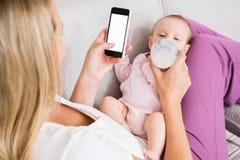 Madre que usa el teléfono móvil mientras que alimenta a su bebé con la botella de leche Imagenes de archivo