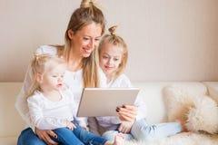 Madre que usa la tableta así como sus hijas imágenes de archivo libres de regalías