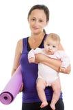 Madre que va a hacer ejercicios de la aptitud con su bebé Foto de archivo libre de regalías