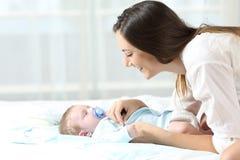 Madre que viste a su hijo del bebé Fotografía de archivo