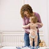 Madre que viste a su hijo en dormitorio Fotografía de archivo libre de regalías