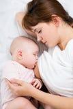 Madre Relaxed che allatta al seno la sua neonata Fotografia Stock