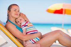 Madre Relaxed en bebé de abarcamiento de la cama del sol Imagenes de archivo