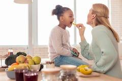 madre Rubio-cabelluda que alimenta a su muchacha divertida linda con las frutas imagen de archivo