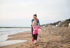 Madre sana y bebé que corren en la playa Fotos de archivo