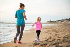 Madre sana y bebé que corren en la playa Imagenes de archivo