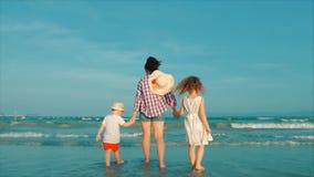 Madre silueteada e hija e hijo felices que juegan y que se divierten en la playa en la puesta del sol C?mara lenta Familia feliz almacen de metraje de vídeo