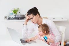 Madre sollecitata con il bambino che per mezzo del computer portatile a casa Fotografie Stock Libere da Diritti