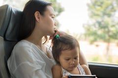 Madre sollecitata Tired che viaggia con il suo bambino sul bus Disordine di depressione fotografia stock