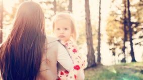 Madre soltera joven que celebra a la hija linda de la niña pequeña en sus brazos y que frota ligeramente su pelo, concepto del po Imagenes de archivo