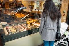 Madre soltera que admira los pasteles dulces franceses en ventana de la panadería Fotos de archivo libres de regalías