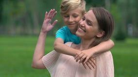 Madre soltera que se ocupa al hijo en el parque, abrazando al niño querido, adopción almacen de metraje de vídeo