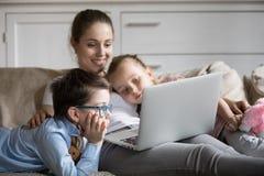 Madre soltera y dos niños que miran película en el ordenador portátil imagenes de archivo