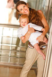 Madre sonriente con el bebé que mira hacia fuera del elevador Imagen de archivo libre de regalías