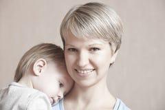 Madre sonriente con el bebé que se inclina en sus hombros Foto de archivo