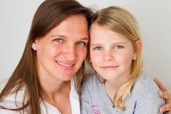 Madre sonriente con la hija Imagenes de archivo