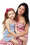 Madre sonriente con la hija en sus rodillas Fotografía de archivo
