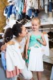 Madre sonriente con los pijamas de compra del bebé de la hija en la sección de los niños Imagenes de archivo