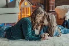 Madre sonriente con su hija en el cuarto en la alfombra imagen de archivo libre de regalías