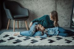 Madre sonriente con su hija en el cuarto en la alfombra fotos de archivo