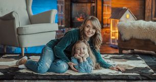 Madre sonriente con su hija en el cuarto en la alfombra foto de archivo