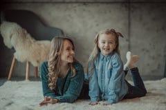 Madre sonriente con su hija en el cuarto en la alfombra fotografía de archivo