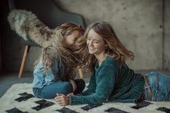 Madre sonriente con su hija en el cuarto en la alfombra foto de archivo libre de regalías