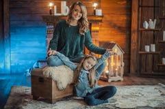 Madre sonriente con su hija en el cuarto en la alfombra imagen de archivo