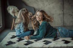 Madre sonriente con su hija en el cuarto en la alfombra imagenes de archivo