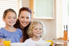 Madre sonriente con sus niños en la cocina Fotografía de archivo libre de regalías