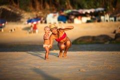Madre sonriente con un niño en la playa Imagen de archivo