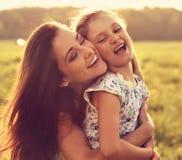 Madre sonriente de goce feliz que abraza a su niño de risa juguetón g Foto de archivo