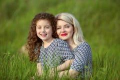Madre sonriente e hija divertida en campo de hierba verde outdoor Fotos de archivo libres de regalías