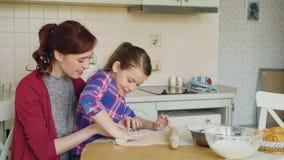 Madre sonriente e hija linda que hacen las galletas de la Navidad junto que se sientan en la tabla de cocina en casa Familia, com