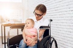 Madre sonriente en la silla de ruedas que abraza al bebé recién nacido imagen de archivo libre de regalías