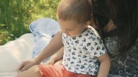 Madre sonriente feliz con el hijo del bebé en comida campestre Concepto de familia feliz almacen de metraje de vídeo