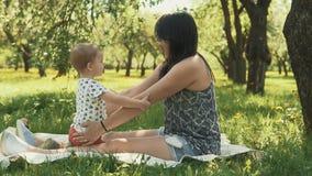 Madre sonriente feliz con el hijo del bebé en comida campestre debajo del árbol grande Concepto de familia almacen de video