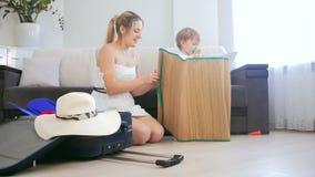 Madre sonriente feliz con el hijo del bebé que juega mientras que embala la maleta para las vacaciones de verano almacen de video