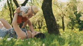 Madre sonriente feliz con el hijo lindo en comida campestre debajo del árbol grande Concepto de familia metrajes