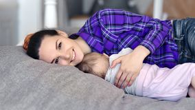 Madre sonriente joven que cuida que abraza al bebé durmiente que mira el tiro medio de la cámara metrajes