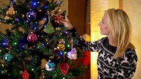 Madre sonriente que adorna el árbol de navidad almacen de metraje de vídeo