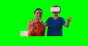 Madre sonriente que ayuda al hijo al usar las auriculares 4k de la realidad virtual metrajes